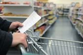 stock photo of crisps  - Hand pushing a shopping cart through the aisles of a supermarket - JPG