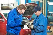 picture of internal combustion  - two mechanic engineers examining spare part of internal combustion engine of automobile car at repair service station - JPG