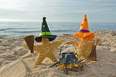 foto of broom  - Starfish with witch hats and broom on the beach - JPG