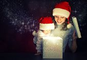 stock photo of blinking  - Christmas magic gift box and a woman happy family mother and Child baby - JPG