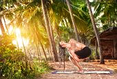 image of dreadlocks  - Yoga twisted pose by fit man with dreadlocks on the beach near the fishermen hut in Varkala Kerala India - JPG