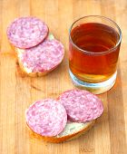 stock photo of tumbler  - open sandwich with sausage and hot tea in the glass tumbler - JPG