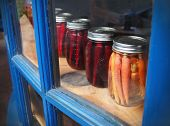 stock photo of parsnips  - A row of carrots and parsnips pickled in mason jars is displayed in a glass window cabinet with blue frames - JPG