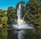 Fountain  And Rainbow In Riga Canal, That Flows Through Bastion Park (bastejkalns). Latvia