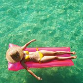 foto of mattress  - Woman relaxing on inflatable mattress at the beach - JPG