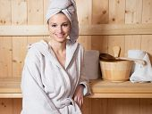 image of sauna woman  - Young attractive woman smiling and relaxing in sauna at spa - JPG