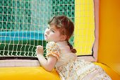picture of bounce house  - Little beautiful girl in dress stands in yellow bouncy castle and looks through net