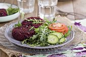 stock photo of veggie burger  - Vegan burgers with beetroot and beans served with fresh vegetables - JPG
