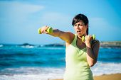 stock photo of punch  - Fitness woman punching hard for working out with dumbbells on beach - JPG