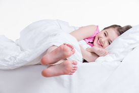 picture of nighties  - Adorable happy little girl in pink nightie awake in the bed on a white background - JPG
