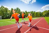 picture of relay  - Three girls with one relay baton running in race on stadium - JPG