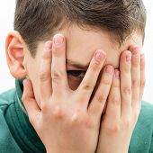 stock photo of cunning  - Teen covered his face - JPG
