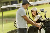 foto of caddy  - Young couple playing golf at the golf court - JPG