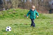 stock photo of little-league  - Little boy playing football or soccer on cold sping or autumn day - JPG