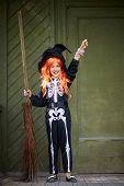 stock photo of antichrist  - Portrait of happy Halloween girl in spooky costume - JPG