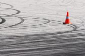 image of skid  - Orange traffic cone and curved car drift skid marks - JPG