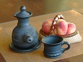 stock photo of loamy  - Arabian style coffee pot and ceramic vase with peaches on a table - JPG