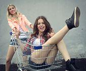 foto of adoration  - Two happy beautiful teen girls driving shopping cart outdoor - JPG