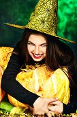 pic of teen smoking  - Pretty teen girl in a costume of witch standing with pumpkins over dark smoky background - JPG