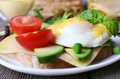 picture of benediction  - Toast with egg Benedict and avocado on plate on wooden table - JPG