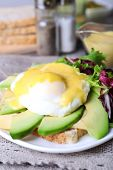 image of benediction  - Toast with egg Benedict and avocado on plate on table close up - JPG