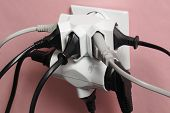 image of dangerous  - Dangerous multiple electric plugs in wall outlet - JPG