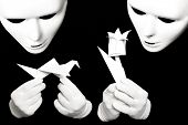 stock photo of shadoof  - White theatrical mask and paper origami isolated on black - JPG