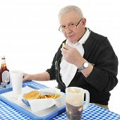 picture of bifocals  - A senior adult man looking up at the viewer as he enjoys a french fry from his fast food basket - JPG
