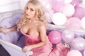 image of romantic  - Romantic beautiful blonde woman in pink dress posing over balloons looking at camera - JPG