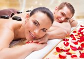 stock photo of hot couple  - Portrait of happy smiling couple relaxing in spa salon with hot stones on body - JPG