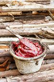 image of grease  - Close up dirty grease and wooden paddle in old bucket on heap of lumber - JPG