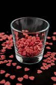 picture of glass heart  - A glass full of red hearts on a black background covered with red hearts - JPG