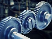 stock photo of machinery  - Close up of three cog wheels with machinery in background  - JPG