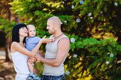 stock photo of cross-dress  - Happy young family, father-in a gray T-shirt and blue jeans with very short hair and a cross around his neck, her mother-in white dress with black long straight hair and brown-eyed son boy in blue shirt, fun, and relaxing in the summer park.