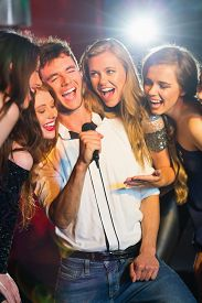 foto of karaoke  - Happy friends singing karaoke together in a bar - JPG