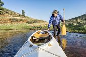 picture of horsetooth reservoir  - senior paddler and decked expedition canoe on the shore of Horsetooth Reservoir - JPG