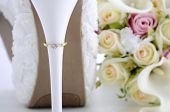 picture of stiletto heels  - Wedding Day concept with rings on heel of beautiful white floral bridal stiletto shoes with bouquet on white shabby chic wood table - JPG