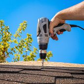 stock photo of roof tile  - The man puts a soft roof on a house roof - JPG