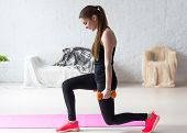picture of butts  - Athletic woman warming up doing weighted lunges with dumbbells workout exercise for butt legs at home healthy lifestyle sport bodybuilding concept - JPG