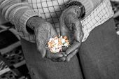 Picture of old woman is holding medications in her hands.