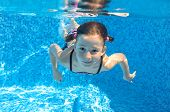 foto of swimming  - Happy child swims in pool underwater - JPG