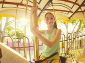 pic of carnival ride  - Cute smiling little girl riding on a Carnival Carousel at an amusement park or theme park - JPG