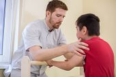 foto of physiotherapy  - Doctor supports the child during physiotherapy treatment - JPG