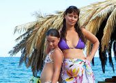 image of deserted island  - Beautiful family of mother and daughter have vacation at tropical island near palm hut - JPG