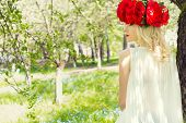 pic of woman red blouse  - beautiful young gentle elegant young blond woman with red peony in a wreath of white blouse walking in the lush apple orchard - JPG