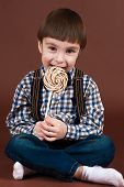 pic of lollipop  - handsome boy eating lollipop sitting on the floor isolated on brown background - JPG