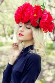 image of woman red blouse  - beautiful young gentle elegant young blond woman with a red crown of peony in a black blouse walks in the lush apple orchard - JPG