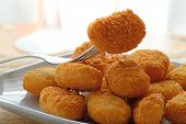 foto of gold nugget  - chicken nuggets served in a white bowl on a white wooden table of a rustic kitchen - JPG