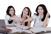 foto of joining hands  - Portrait of three beautiful schoolgirls joining hands together isolated on white background - JPG
