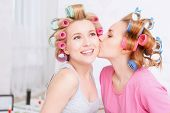 foto of pajamas  - Friendship. Young blond girl kissing her best friend at her cheek smiling and wearing pajamas and colorful hair rollers at home party in the light room